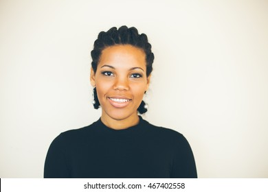 Beautiful African american woman making faces in front of the white wall.