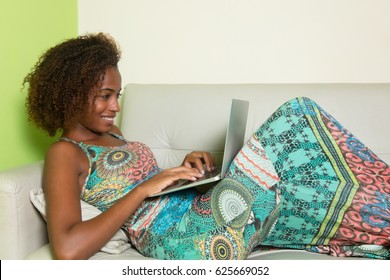 Beautiful african american woman with notebook on couch