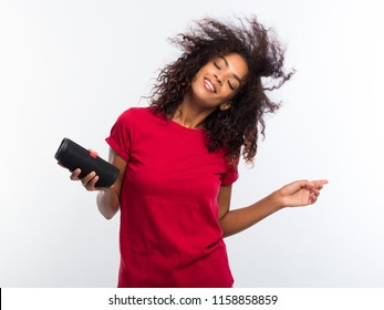 Beautiful african american woman in red t-shirt enjoying and dancing at white background. Modern trendy girl with afro hairstyle listening to music by wireless portable speaker