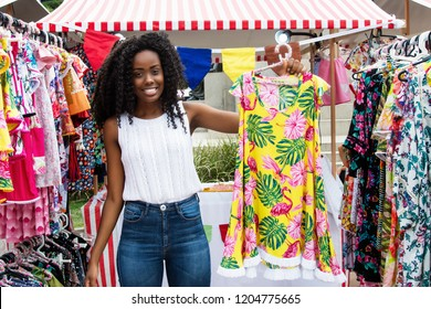 Beautiful african american woman selling clothes to customers at typical market