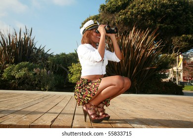 a beautiful african american woman in a short skirt and a captains hat at the beach with binoculars