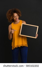 Beautiful African American woman showing something on a chalkboard