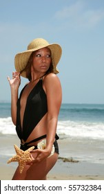 a beautiful african american woman shows off the star fish she found on the beach