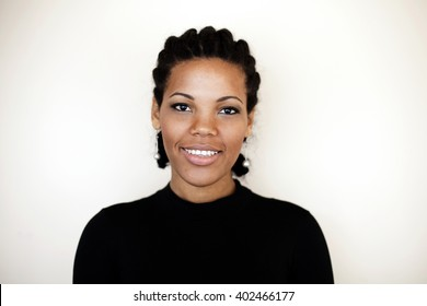Beautiful african american woman smiling in front white wall.