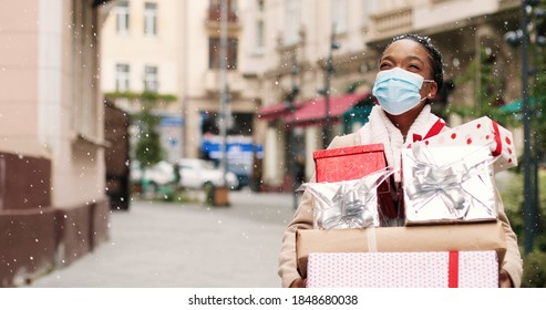 Beautiful African American woman walking in decorated city with many christmas gift boxes after xmas shopping. Portrait of joyful grateful female in mask holds holiday presents. Surprise gifts concept - Shutterstock ID 1848680038