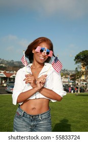 a beautiful african american woman wears american flag glasses and waves american flags for the 4th of july