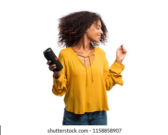 Beautiful african american woman in yellow top enjoying and dancing at white background. Modern trendy girl with afro hairstyle listening to music by wireless portable speaker
