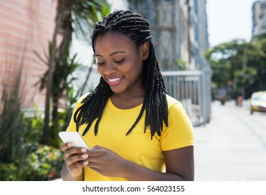 Beautiful african american woman in a yellow shirt texting message with mobile phone