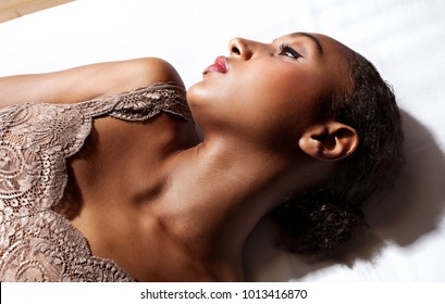 Beautiful african american young woman laying on home bed serene and thoughtful wearing lingerie, bedroom indoors. Healthy black female relaxing, moody lifestyle, dark flawless skin. Beauty leisure.