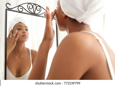 Beautiful african american young woman getting ready in home bathroom with towel on hair, applying make up, grooming. Black female cosmetics, mirror face reflection, vanity lifestyle.