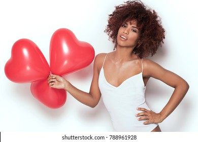 Beautiful african american young woman holding red heart shaped baloons, valentines day.