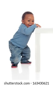 Beautiful african baby standing with a table isolated on a white background