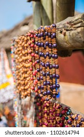 Beautiful African beaded necklaces hanging from a wood beam in an open air market