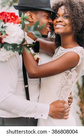 Beautiful african bride and happy groonm in black hat  embracing on the weddig ceremont close up