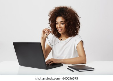 Beautiful african businesswoman looking at laptop screen over white background.