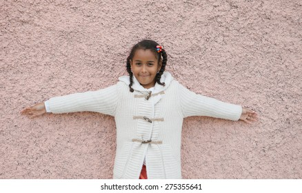 Beautiful african child with a brick a pink wall of background