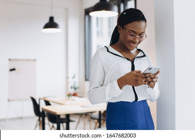 Beautiful african corporate worker talking on mobile phone in modern office