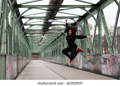 Beautiful African dancehall dancer jumping on a bridge