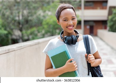 beautiful african female college student with headphones on campus
