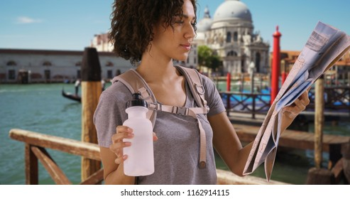 Beautiful African female drinks water and reads map near boat dock in Venice