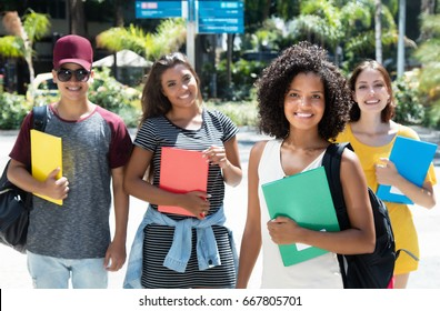 Beautiful african female student with group of international students outdoor in the city in the summer