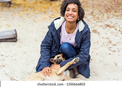 beautiful african girl in autumn park on nature plays with a dog