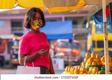 A beautiful African girl buying from local market and wearing a face mask for protection - concept on black millennial buying from market during covid-19 pandemic - Africa fruits and veggies market.