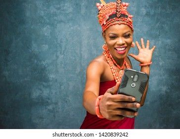 beautiful african girl dressed in cultural attire feeling very happy and excited while looking at her phone she is holding