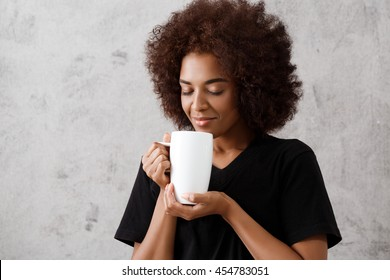 Beautiful african girl holding cup, eyes closed, over light background.