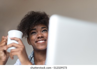 Beautiful african girl holding cup over light background.