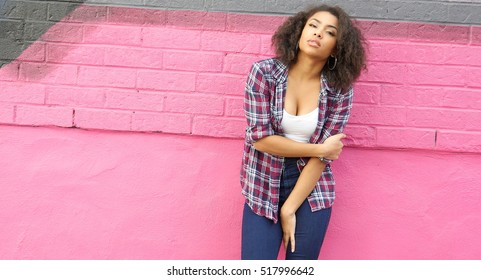 Beautiful African girl on pink wall background in urban scene