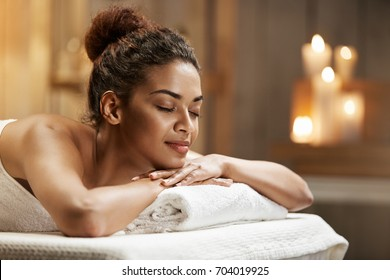 Beautiful african girl resting relaxing in spa resort with closed eyes.