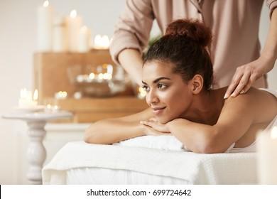 Beautiful african girl smiling enjoying massage in spa resort.