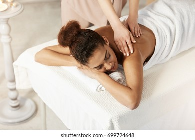 Beautiful african girl smiling enjoying massage with closed eyes in spa salon.