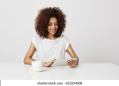 Beautiful african girl smiling looking at tablet over white background. Copy space.