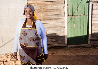 Beautiful african lady in her traditional clothes at her township house.