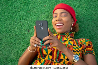 a beautiful african lady laying on the floor in a park using her mobile phone