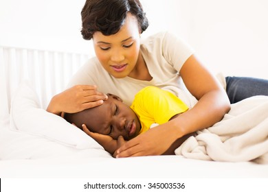 beautiful african mother embracing her sick son