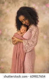 Beautiful African mother in pink lace dress holding her 1 week old little baby