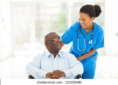 beautiful african nurse taking care of senior patient in wheelchair