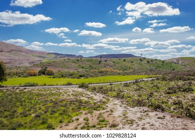 Beautiful African scenery in Morocco, green fields, blue sky, red sands