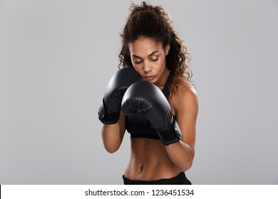 Beautiful african sportswoman isolated over gray background, doing exercises with boxing gloves