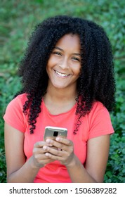 Beautiful african teenager girl with a mobile in a park