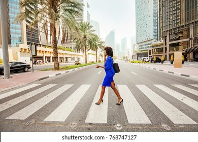 Beautiful African woman crossing the road on a street of Dubai
