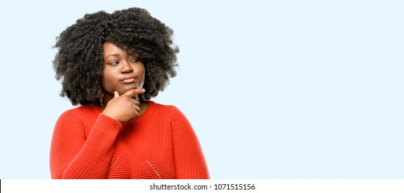 Beautiful african woman doubt expression, confuse and wonder concept, uncertain future, blue background