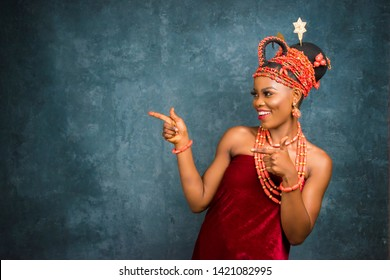 beautiful african woman dressed in traditional bridal attire smiling and pointing to her side