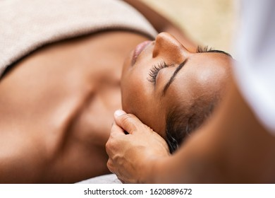 Beautiful african woman getting face massage in beauty spa. Black girl with closed eyes relaxing in outdoor spa while getting head massage. Serene woman relaxing outdoor in a beauty center.