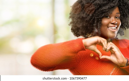 Beautiful african woman happy showing love with hands in heart shape expressing healthy and marriage symbol, outdoor