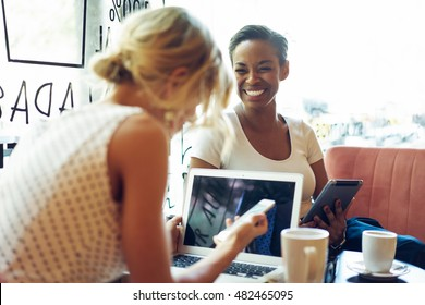 Beautiful african woman is laughing while her friend is looking at the screen of a mobile phone in a coffee shop. Friends are having fun while sitting in an urban restaurant with electronic devices.
