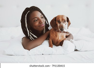A beautiful African woman lies on her stomach, on a bed with a red dog dachshund, a domestic pet. Good morning. Portrait. Nigeria, Africa.